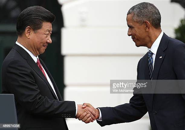S President Barack Obama shakes hands with Chinese President Xi Jinping during a state arrival ceremony on the south lawn of the White House grounds...