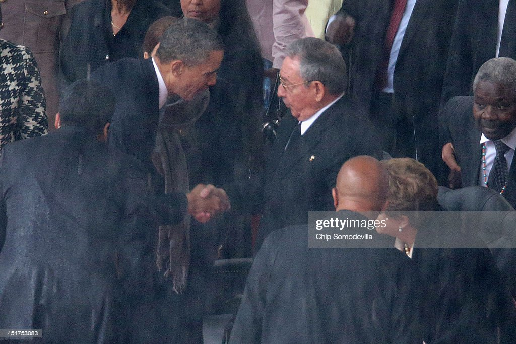 U.S. President <a gi-track='captionPersonalityLinkClicked' href=/galleries/search?phrase=Barack+Obama&family=editorial&specificpeople=203260 ng-click='$event.stopPropagation()'>Barack Obama</a> (L) shakes hands with Cuban President <a gi-track='captionPersonalityLinkClicked' href=/galleries/search?phrase=Raul+Castro&family=editorial&specificpeople=239452 ng-click='$event.stopPropagation()'>Raul Castro</a> during the official memorial service for former South African President Nelson Mandela at FNB Stadium December 10, 2013 in Johannesburg, South Africa. Over 60 heads of state have travelled to South Africa to attend a week of events commemorating the life of former South African President Nelson Mandela. Mr Mandela passed away on the evening of December 5, 2013 at his home in Houghton at the age of 95. Mandela became South Africa's first black president in 1994 after spending 27 years in jail for his activism against apartheid in a racially-divided South Africa.