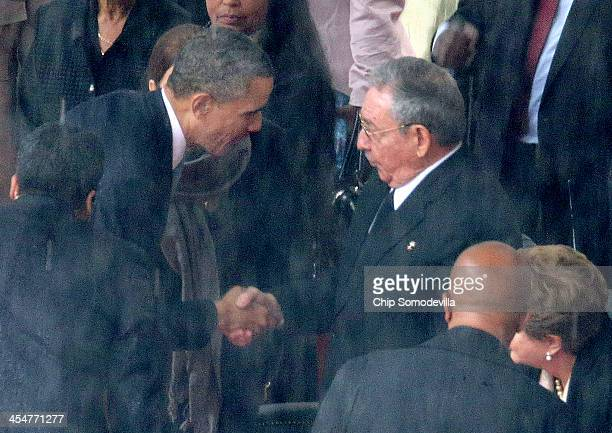 US President Barack Obama shakes hands with Cuban President Raul Castro during the official memorial service for former South African President...