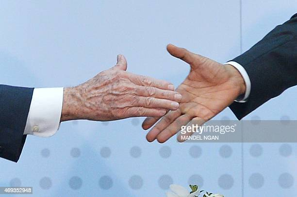 US President Barack Obama shakes hands with Cuba's President Raul Castro on the sidelines of the Summit of the Americas at the ATLAPA Convention...
