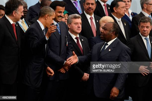 US President Barack Obama shakes hands with Gabonese President Ali Bongo Ondimba during the family photo at the COP21 United Nations Climate Change...
