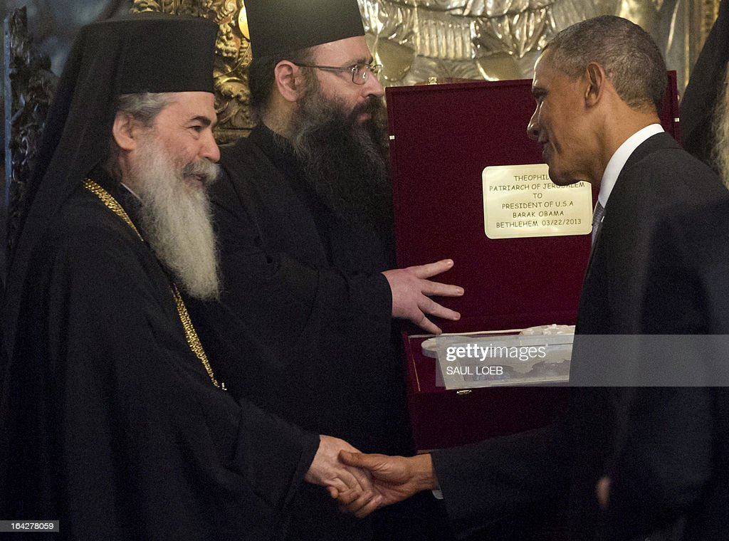 US President Barack Obama shakes hands with Greek Orthodox Patriarch Theopilos III after receiving a gift during a tour the Church of the Nativity, built on the site where tradition says Jesus was born, in the West Bank city of Bethlehem, on March 22, 2013, on the final day of Obama's 3-day trip to Israel and the Palestinian territories. AFP PHOTO / Saul LOEB