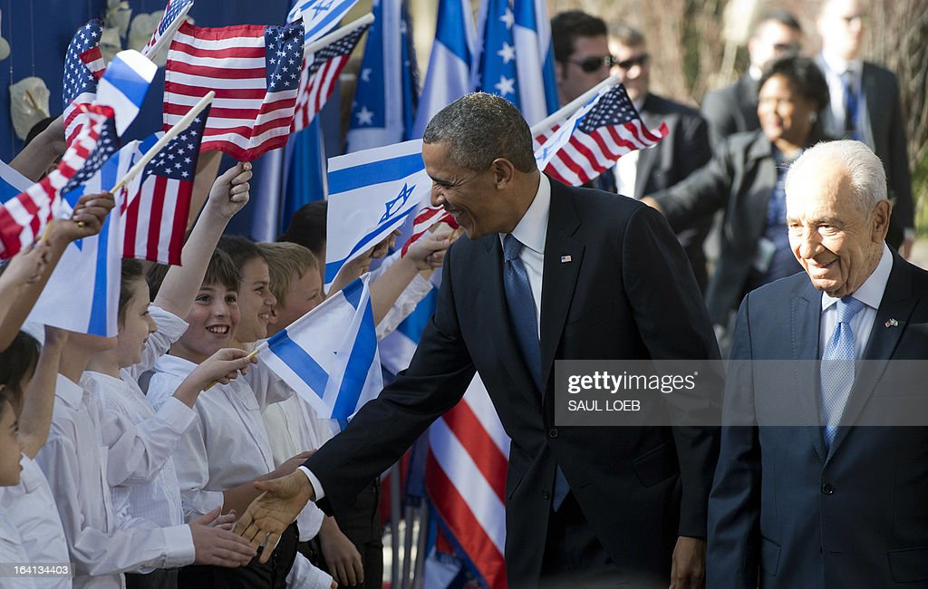 US President Barack Obama (C) shakes hands with Israeli children alongside Israeli President Shimon Peres upon the formers arrival at the President's residence in Jerusalem on March 20, 2013. Obama arrived in Israel for the first time as US president, hoping to ease past tensions with his hosts and under pressure to narrow differences over handling Iran's nuclear threat.