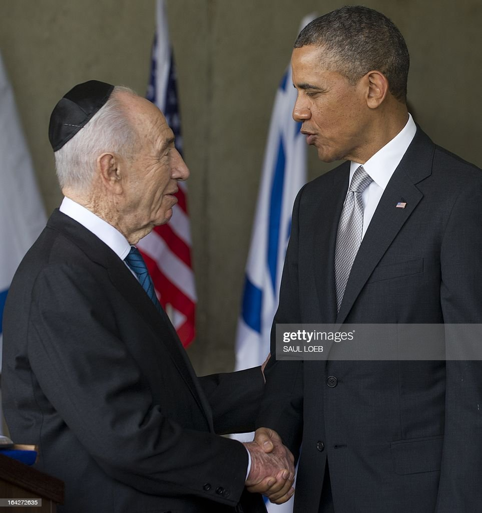 US President Barack Obama shakes hands with Israeli President Shimon Peres (L) after touring Yad Vashem Holocaust Museum in Jerusalem, which commemorates the six million Jewish Holocaust victims killed by the Nazis during World War II, on March 22, 2013, on the final day of Obama's 3-day trip to Israel and the Palestinian territories. AFP PHOTO / Saul LOEB