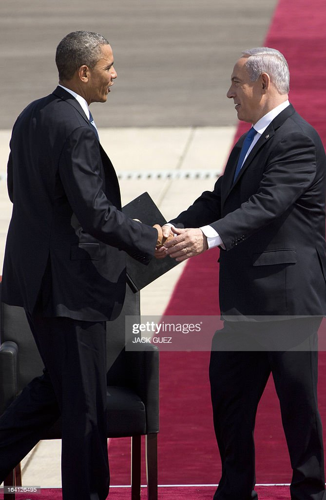 US President Barack Obama (L) shakes hands with Israeli Prime Minister Benjamin Netanyahu during a welcome ceremony at Israel's International Ben Gurion airport on March 20, 2013. Obama landed in Israel for the first time as US president, on a mission to ease past tensions with his hosts and hoping to paper over differences on handling Iran's nuclear threat.