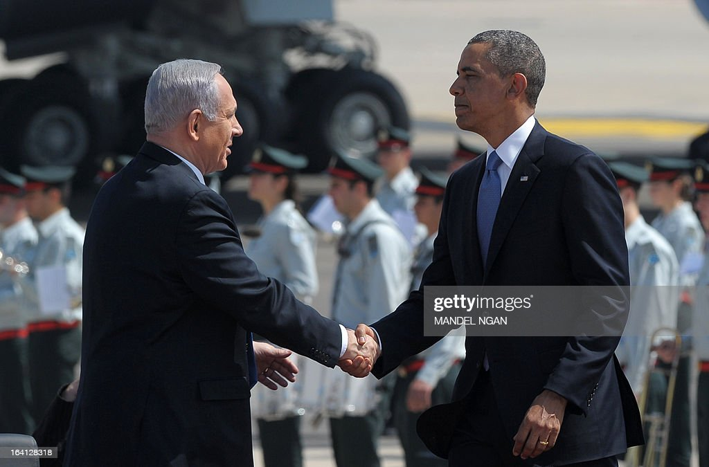US President Barack Obama (R) shakes hands with Israeli Prime Minister Benjamin Netanyahu (L) during a welcome ceremony at Ben Gurion International Airport on March 20, 2013 near Tel Aviv. Obama landed in Israel for the first time as US president, on a mission to ease past tensions with his hosts and hoping to paper over differences on handling Iran's nuclear threat.