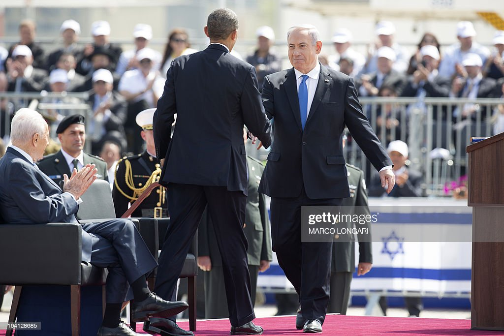 US President Barack Obama (R) shakes hands with Israeli Prime Minister Benjamin Netanyahu (L) during a welcome ceremony at Ben Gurion International Airport on March 20, 2013 near Tel Aviv. Obama landed in Israel for the first time as US president, on a mission to ease past tensions with his hosts and hoping to paper over differences on handling Iran's nuclear threat. AFP PHOTO/MARCO LONGARI