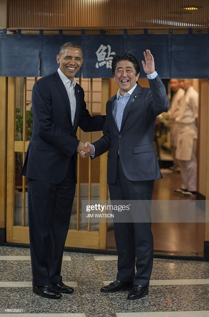 US President Barack Obama (L) shakes hands with Japanese Prime Minister Shinzo Abe before a private dinner at Sukiyabashi Jiro restaurant in Tokyo on April 23, 2014. Obama landed in Tokyo on April 23 to launch an Asian tour dedicated to reinvigorating his policy of 'rebalancing' US foreign policy towards a dynamic Asia. Sukiyabashi Jiro's less-than-plush surroundings notwithstanding, it is the proud possessor of three Michelin stars, and people flock to pay a minimum $300 for 20 pieces of sushi chosen by the 88-year-old patron, Jiro Ono. AFP PHOTO / Jim WATSON