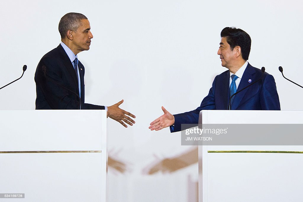 US President Barack Obama(L) shakes hands with Japanese Prime Minister Shinzo Abe during the Group of Seven (G7) summit meetings in Shima on May 25, 2016. / AFP / JIM