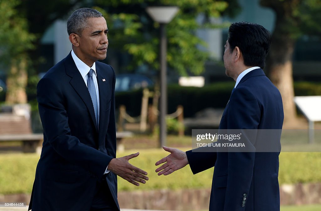 US President Barack Obama (L) shakes hands with Japanese Prime Minister Shinzo Abe (R) after laying a wreath at the cenotoph in the Peace Momorial park in Hiroshima on May 27, 2016. Obama became the first sitting US leader to visit the site that ushered in the age of nuclear conflict. / AFP / TOSHIFUMI