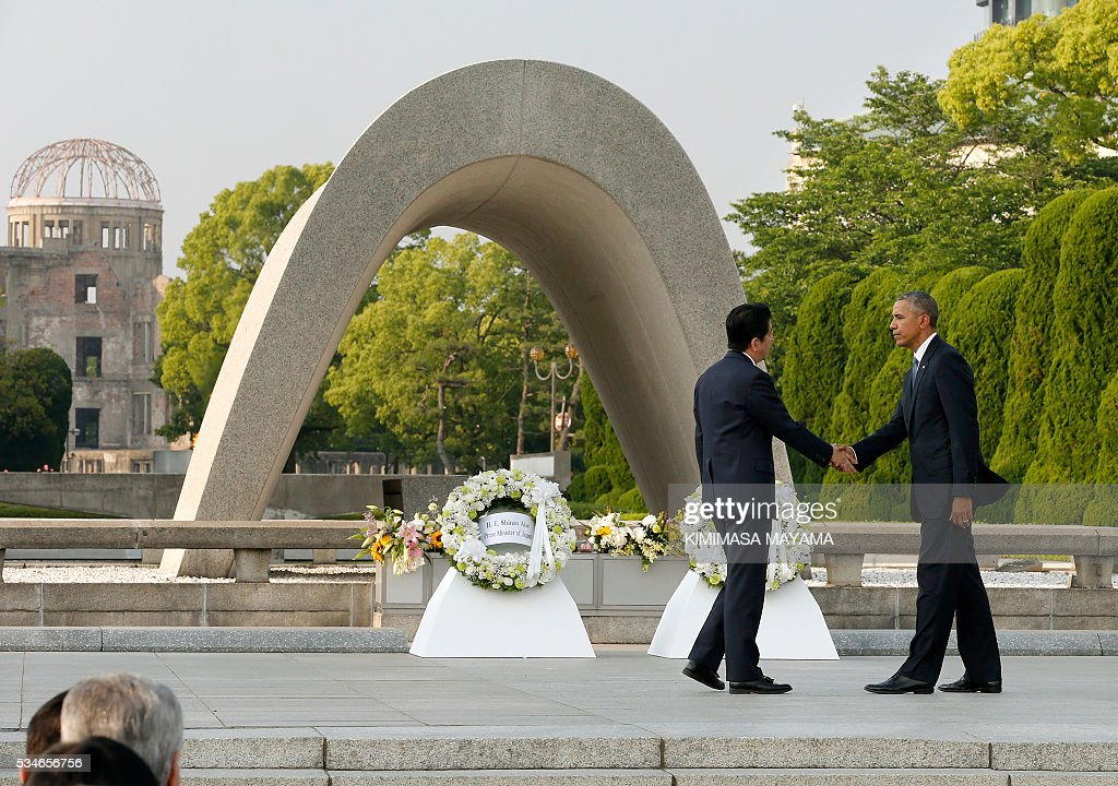US President Barack Obama (R) shakes hands with Japanese Prime Minister Shinzo Abe (L) after laying a wreath in front of the cenotaph to offer a prayer for victims of the atomic bombing in 1945 at Hiroshima Peace Memorial Park in Hiroshima on May 27, 2016. Obama on May 27 paid moving tribute to victims of the world's first nuclear attack. MAYAMA