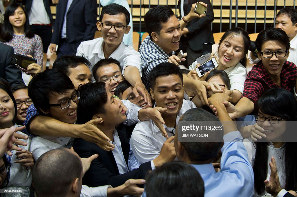 US President Barack Obama (bottom R) shakes hands with members of the audience after speaking at the Young Southeast Asian Leaders Initiative town hall event in Ho Chi Minh City on May 25, 2016. Obama urged communist Vietnam on May 24 to abandon authoritarianism, saying basic human rights would not jeopardise its stability, after Hanoi barred several dissidents from meeting the US leader. / AFP / JIM