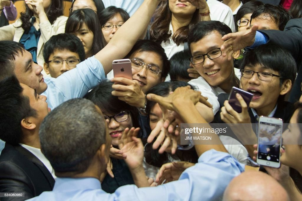 US President Barack Obama (bottom L) shakes hands with members of the audience after speaking at the Young Southeast Asian Leaders Initiative town hall event in Ho Chi Minh City on May 25, 2016. Obama urged communist Vietnam on May 24 to abandon authoritarianism, saying basic human rights would not jeopardise its stability, after Hanoi barred several dissidents from meeting the US leader. / AFP / JIM