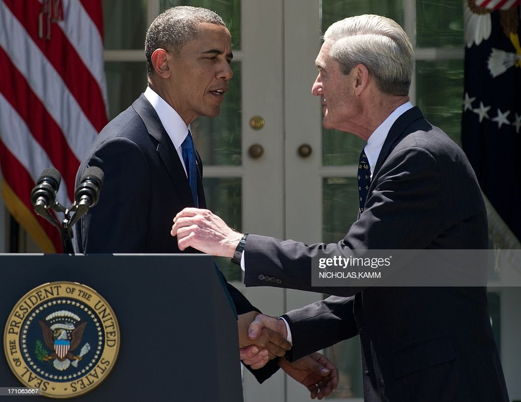 US President Barack Obama shakes hands with outgoing Federal Bureau of Investigations (FBI) director Robert Mueller in the Rose Garden at the White House in Washington on June 21, 2013 as he nominates Jim Comey to be the next FBI director. Comey, a deputy attorney general under George W. Bush, would replace Mueller, who is stepping down from the agency he has led since the week before the September 11, 2001 attacks. AFP PHOTO/Nicholas KAMM