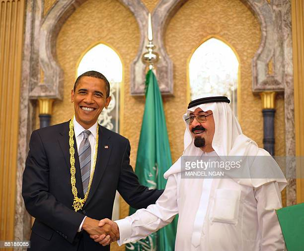 US President Barack Obama shakes hands with Saudi King Abdullah bin Abdul Aziz alSaud after he was presented with the King Abdul Aziz Order of Merit...