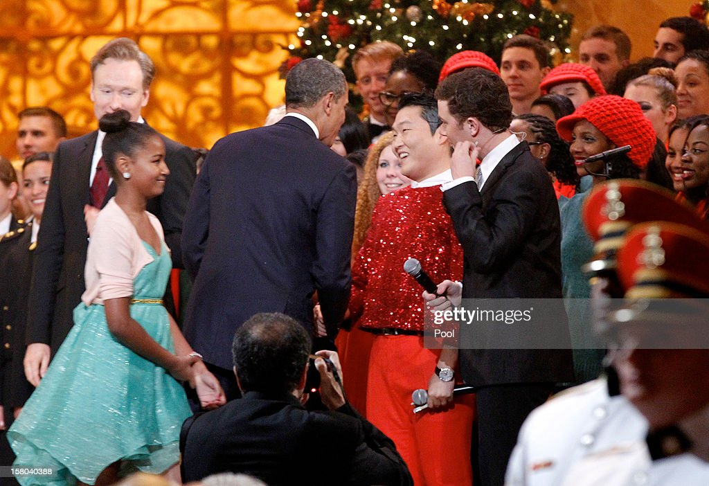 U.S. President Barack Obama shakes hands with South Korean musician PSY (C), next to host Conan O'Brien (L) and performer Scotty McCreery (R) during the 'Christmas in Washington' concert at the National Building Museum on December 9, 2012 in Washington, D.C. The concert benefits the National Childrens Medical Center and is hosted by comedian Conan O'Brien.