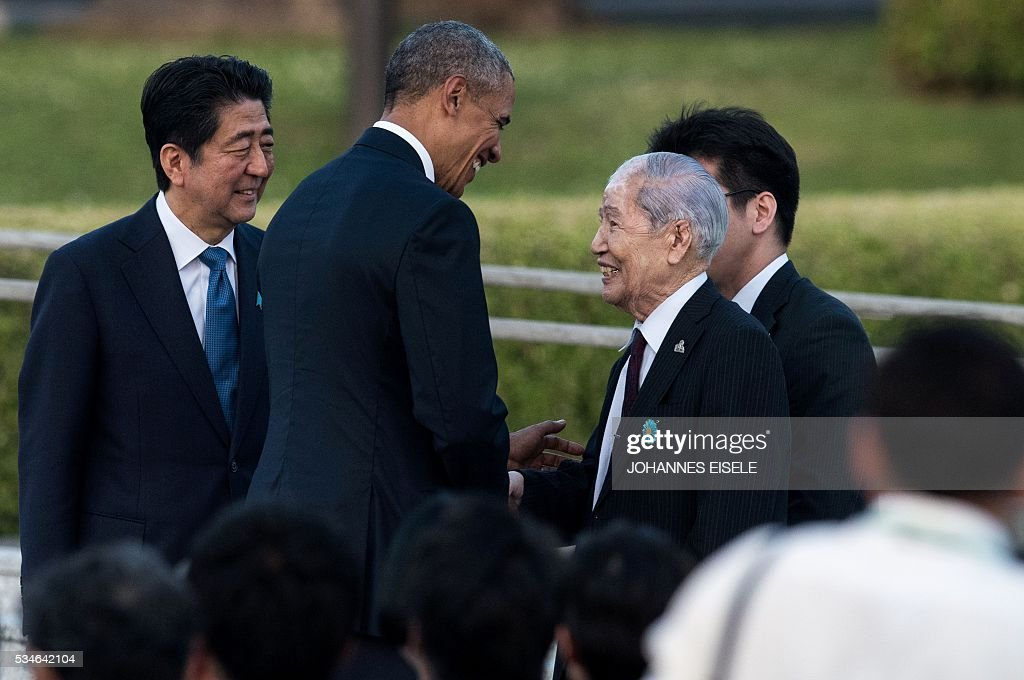 US President Barack Obama (2nd L) shakes hands with Sunao Tsuboi, a survivor of the atomic bombing of Hiroshima, as Japanese Prime Minister Shinzo Abe (L) looks on at the Hiroshima Peace Memorial park cenotaph in Hiroshima on May 27, 2016. Obama became the first sitting US leader to visit the site that ushered in the age of nuclear conflict. / AFP / JOHANNES