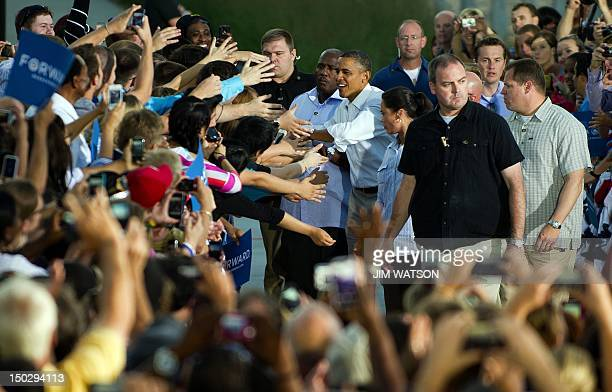 US President Barack Obama shakes hands with supporters as he arrives at Waterloo Center for the Arts in Waterloo Iowa August 14 2012 during his...