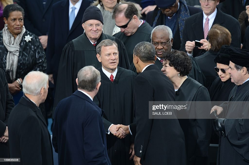 US President Barack Obama shakes hands with US Supreme Court Chief Justice John Roberts, Jr (C) as other members of the Supreme Court look on, during the 57th Presidential Inauguration ceremonial swearing-in at the US Capitol on January 21, 2013 in Washington, DC. The oath was administered by US Supreme Court Chief Justice John Roberts, Jr. AFP PHOTO / Saul LOEB