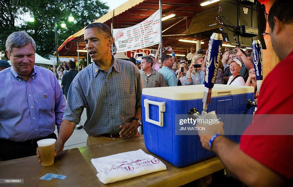 US President Barack Obama (C) shares a beer with US Secretary of Agriculture Tom Vilsack (L) as he visits the Iowa State Fair in Des Moines, Iowa, on August 13, 2012 during an unannounced stop on his three-day campaign bus tour. AFP PHOTO/Jim WATSON
