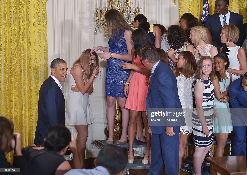 US President Barack Obama (L) shares a laugh with Stefanie Dolson (2L) after she slipped off the riser during an event in honor of the NCAA 2014 Champions, the UConn Huskies Mens and Womens Basketball teams in the East Room of the White House June 9, 2014 in Washington, DC. AFP PHOTO/Mandel NGAN