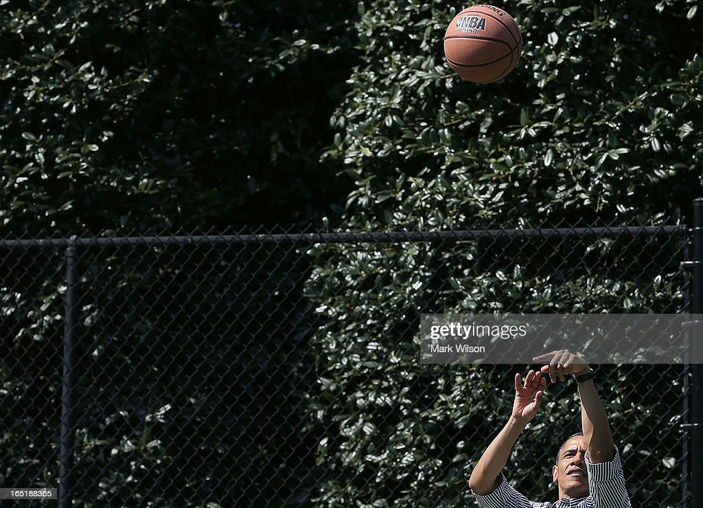 U.S. President Barack Obama shoots the ball while playing basketball with children during the annual Easter Egg Roll on the White House tennis court April 1, 2013 in Washington, DC. Thousands of people are expected to attend the 134-year-old tradition of rolling colored eggs down the White House lawn that was started by President Rutherford B. Hayes in 1878.