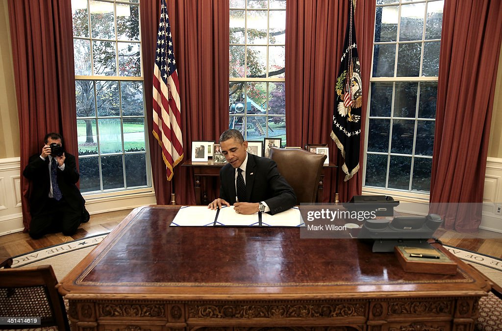 U.S. President <a gi-track='captionPersonalityLinkClicked' href=/galleries/search?phrase=Barack+Obama&family=editorial&specificpeople=203260 ng-click='$event.stopPropagation()'>Barack Obama</a> (R) signs a bill as White House photographer Pete Souza takes pictures behind him in the Oval Office at the White House, on November 21, 2013 in Washington, DC. Obama signed three bills titled H.R. 2747, Streamlining Claims Processing for Federal Contractor Employees Act, S. 330, HIV Organ Policy Equity Act, and S. 893, Veterans Compensation Cost of Living Adjustment Act of 2013.