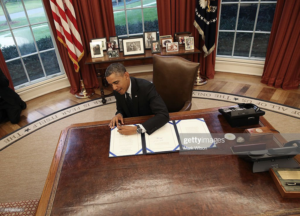 President <a gi-track='captionPersonalityLinkClicked' href=/galleries/search?phrase=Barack+Obama&family=editorial&specificpeople=203260 ng-click='$event.stopPropagation()'>Barack Obama</a> signs a bill in the Oval Office at the White House, on November 21, 2013 in Washington, DC. President Obama signed three bills titled H.R. 2747, Streamlining Claims Processing for Federal Contractor Employees Act, S. 330, HIV Organ Policy Equity Act, and S. 893, Veterans Compensation Cost of Living Adjustment Act of 2013.
