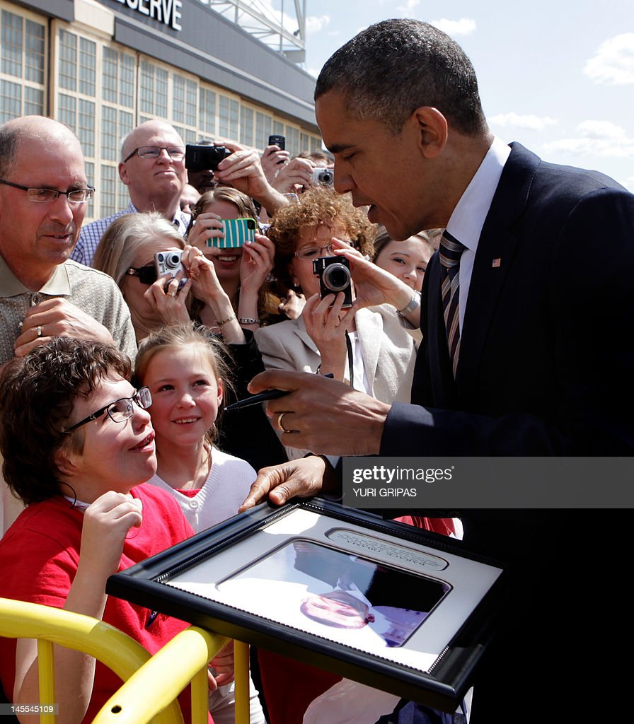 US President Barack Obama (R) signs a framed photograph for Myra Soukup, 16, (L) upon arrival at Minneapolis-Saint Paul International Airport, Minnesota on June 1, 2012. Obama is going to tour the Honeywell Golden Valley facility and attend campaign events.