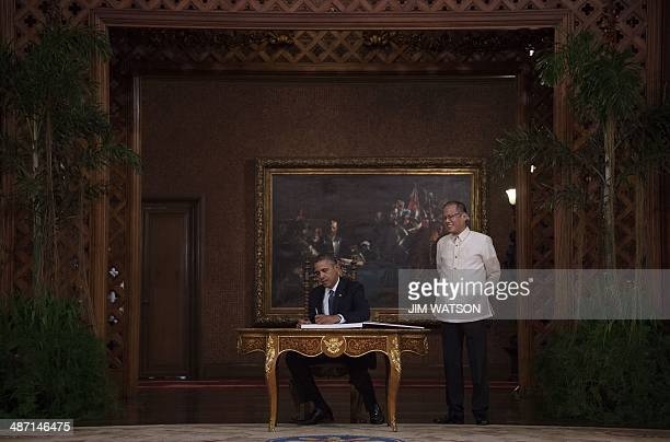 US President Barack Obama signs a guest book as Philippine President Benigno Aquino looks on during a visit to the Malacanang Palace in Manila on...