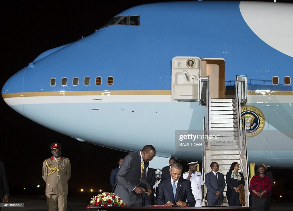 US President Barack Obama signs a guestbook alongside Kenyan President Uhuru Kenyatta upon arrival on Air Force One at Kenyatta International Airport...