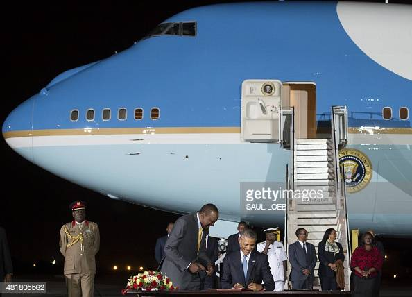 US President Barack Obama signs a guestbook alongside Kenyan President Uhuru Kenyatta upon arrival on Air Force One at Kenyatta International Airport...