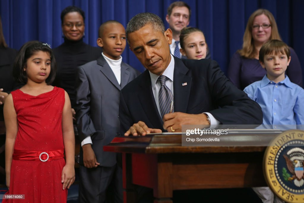 U.S. President Barack Obama signs a series of executive orders about the administration's new gun law proposals as children who wrote letters to the White House about gun violence, (L-R) Hinna Zeejah, Taejah Goode, Julia Stokes and Grant Fritz, look on in the Eisenhower Executive Office building January 16, 2013 in Washington, DC. One month after a massacre that left 20 school children and 6 adults dead in Newtown, Connecticut, the president unveiled a package of gun control proposals that include universal background checks and bans on assault weapons and high-capacity magazines.