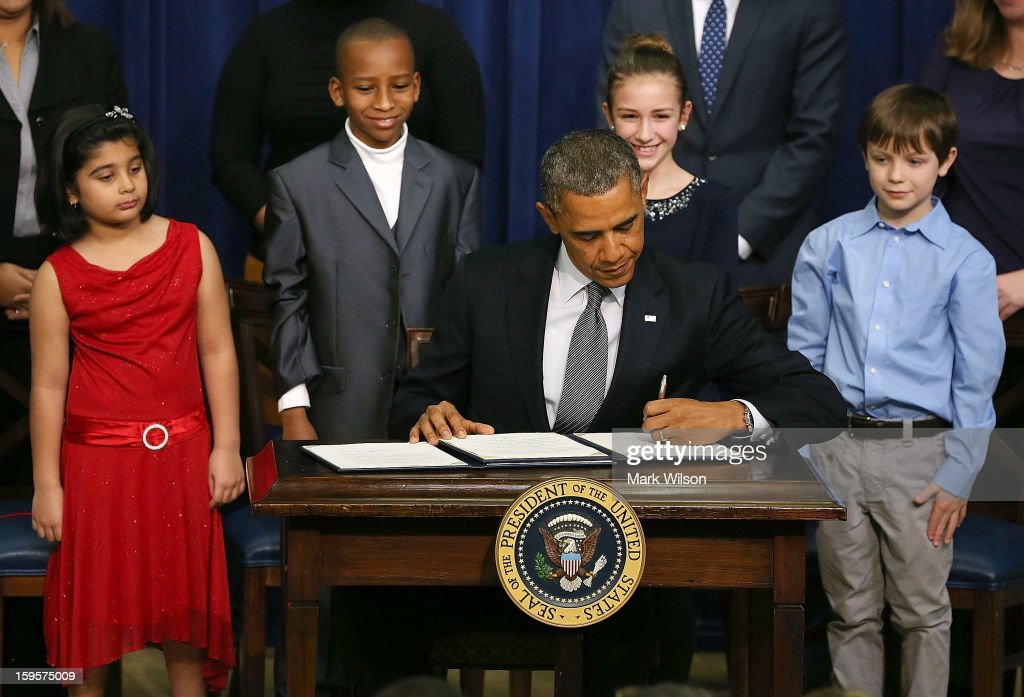 U.S. President Barack Obama signs a series of executive orders about the administration's new gun law proposals as children who wrote letters to the White House about gun violence, (L-R) Hinna Zeejah, Taejah Goode, Julia Stokes and Grant Fritz, look on in the Eisenhower Executive Office building, on January 16, 2012 in Washington, DC. One month after a massacre that left 20 school children and 6 adults dead in Newtown, Connecticut, the president unveiled a package of gun control proposals that include universal background checks and bans on assault weapons and high-capacity magazines.