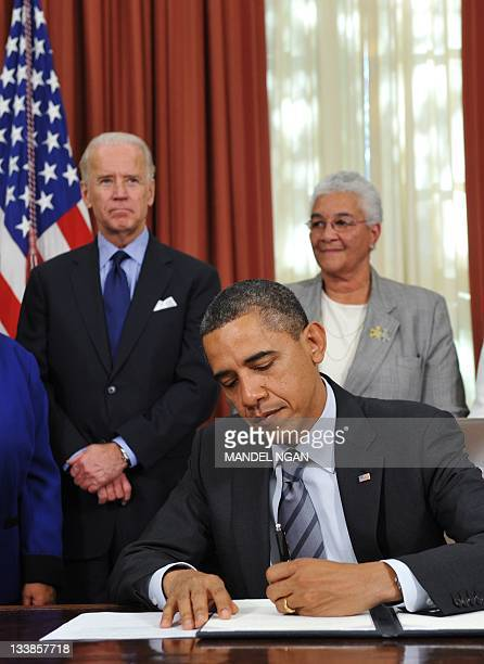 US President Barack Obama signs an executive order to 'cut waste and promote efficient spending' in the federal government November 9 2011 in the...