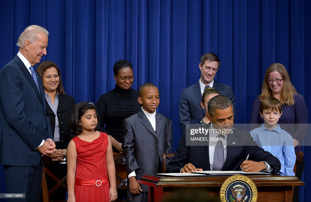 US President Barack Obama signs executive actions to curb gun violence as Vice President Joe Biden(L) and invited guests look on January 16, 2013 in the South Court Auditorium of the Eisenhower Executive Office Building, next to the White House in Washington, DC. President Obama Wednesday signed 23 executive actions to curb gun violence and demand Congress pass an assault weapons ban and other sweeping measures in response to the Newtown massacre. A senior official also said Obama would call on Congress to pass deeper measures, including bans on high-capacity magazine clips of more than 10 rounds and to prohibit armor-piercing bullets. AFP PHOTO/Mandel NGAN
