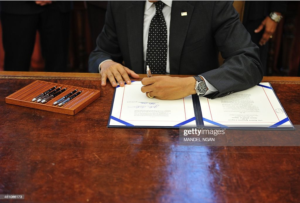 US President Barack Obama signs S. 330, the HIV Organ Policy Equity Act, in the Oval Office of the White House on November 21, 2013 in Washington, DC. AFP PHOTO/Mandel NGAN