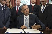 US President Barack Obama signs S 665 the Rafael Ramos and Wenjian Liu National Blue Alert Act of 2015 in the Oval Office of the White House in...