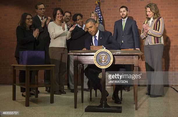 US President Barack Obama signs the 11 trilliondollar omnibus spending bill at the New Executive Office Building across the street from the White...