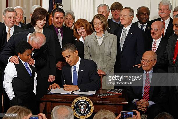 President Barack Obama signs the Affordable Health Care for America Act during a ceremony with fellow Democrats in the East Room of the White House...