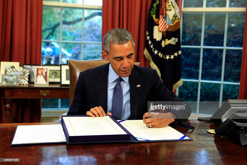 US President Barack Obama signs the bipartisan budget bill 2015 into law in the Oval Office of the White House November 2 2015 in Washington DC Obama...