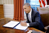 S President Barack Obama signs the Department of Homeland Security funding bill in the Oval Office of the White House March 4 2015 in Washington DC...