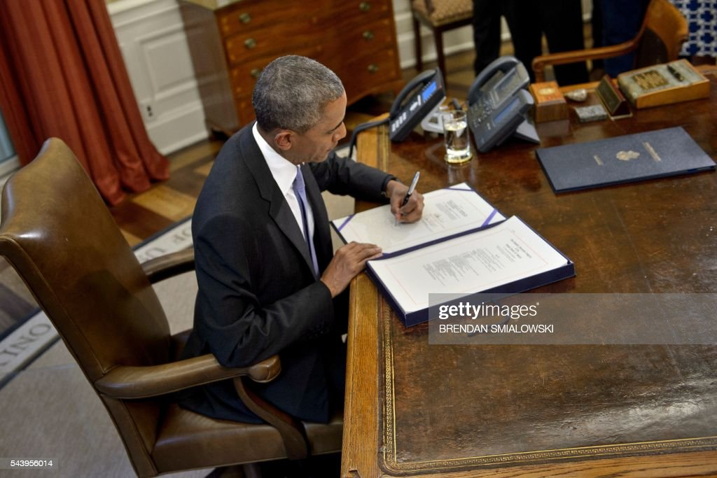 US President Barack Obama signs the Puerto Rico Oversight, Management, and Economic Stability Act, into law in the Oval Office of the White House on June 30, 2016 in Washington, DC. / AFP / Brendan Smialowski
