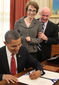 US President Barack Obama signs the Ultralight Aircraft Smuggling Prevention Act of 2012 as former US Rep Gabrielle Giffords and her husband Mark...