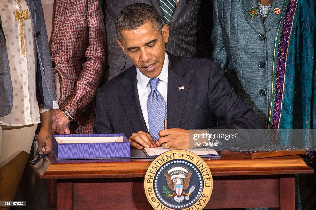 President Barack Obama signs the Violence Against Women Act at the Dept of Interior in Washington DC March 7 2013 Obama was joined by women's...