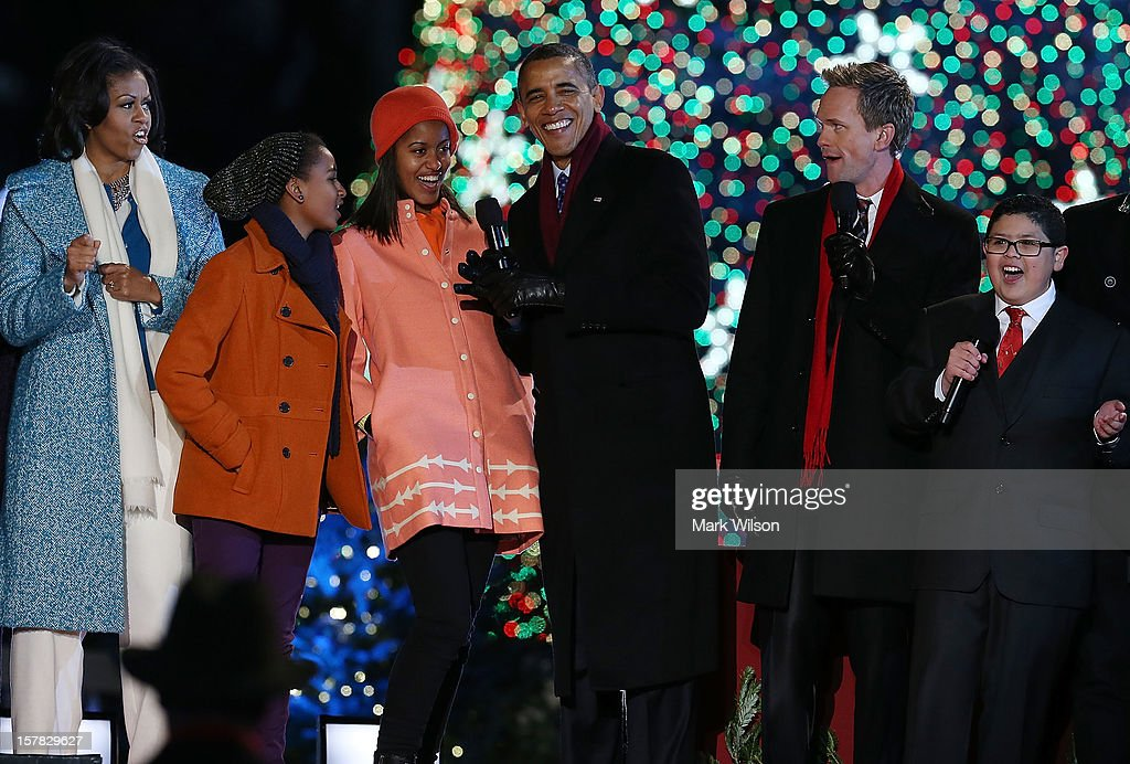U.S. President Barack Obama, sings a Christmas song with his daughters Malia (3rd-L) and Sasha (2nd-L), first lady Michelle Obama (L), Actor Neil Patrick Harris (2nd-R), and Rico Rodriguez (R),during the annual lighting of the National Christmas tree on December 6, 2012 in Washington, DC. This year is the 90th annual National Christmas Tree Lighting Ceremony.