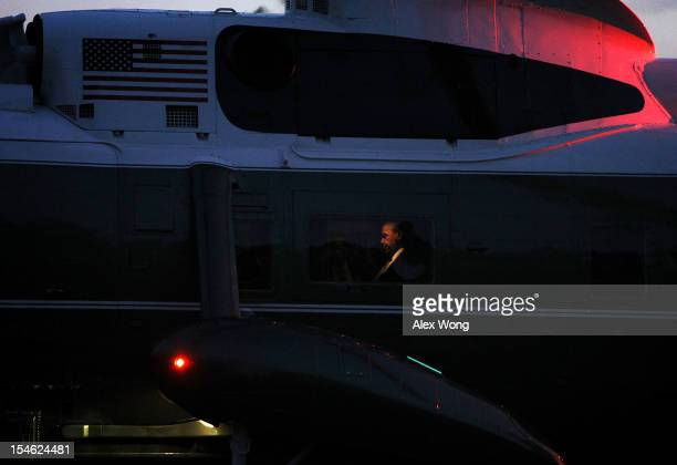 S President Barack Obama sits aboard Marine One as it lands on the South Lawn of the White House October 23 2012 in Washington DC Obama was returning...