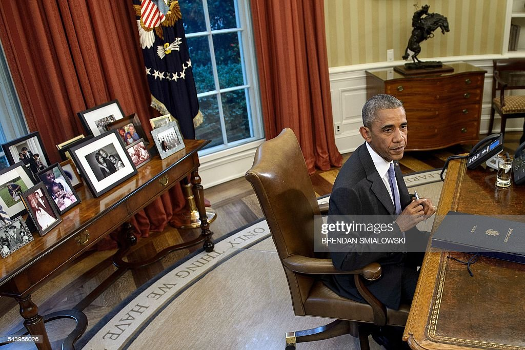 US President Barack Obama sits after signing the Puerto Rico Oversight, Management, and Economic Stability Act, into law in the Oval Office of the White House on June 30, 2016 in Washington, DC. / AFP / Brendan Smialowski