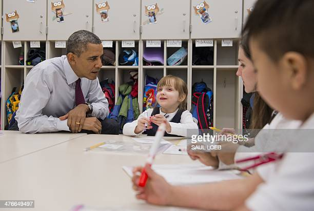 US President Barack Obama sits alongside student Emily Hare during a tour of a PreK classroom at Powell Elementary School prior to speaking on the...