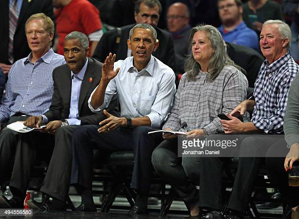 President Barack Obama sits courtside as the Chicago Bulls take on the Cleveland Cavaliers during the season opening game at the United Center on...